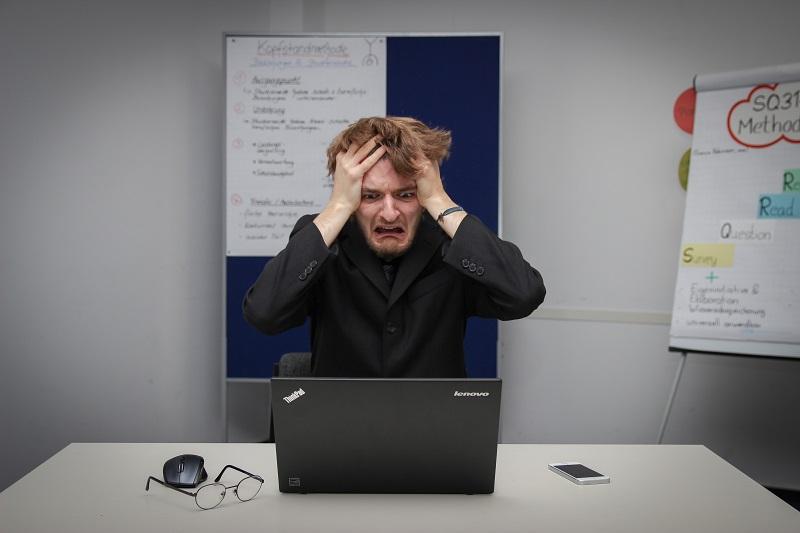 パソコンの前でパニックになっている人