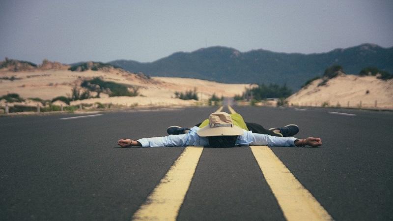 道路の真ん中に寝そべっている人