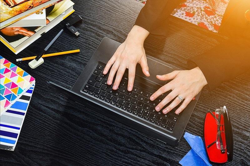 パソコンのキーボードに手が載せられている