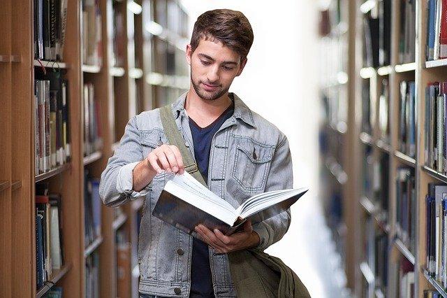 書棚の間で本を読むかっこいい男性