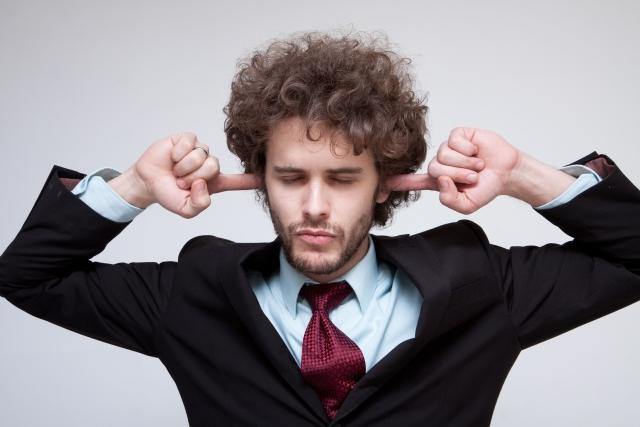 指で耳栓をしている男性