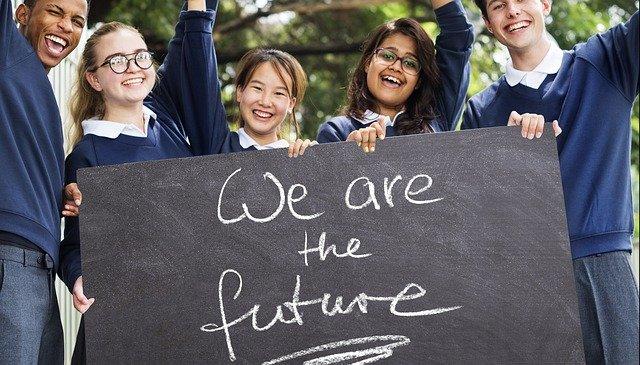 「私たちは未来」と書かれた板を持つ若者