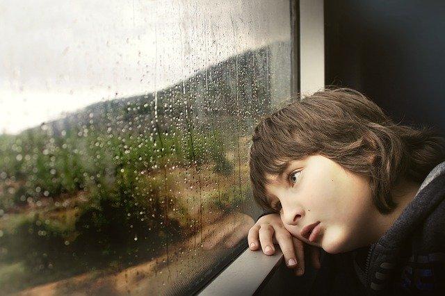 窓の外の雨を眺めている子供