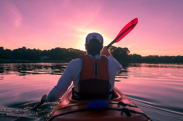 川でカヌーを漕ぐ人の後ろ姿