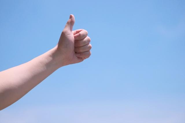 空に向かって親指を立てる