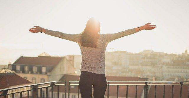 朝、バルコニーで気持ちよさそうに両手を広げる女性
