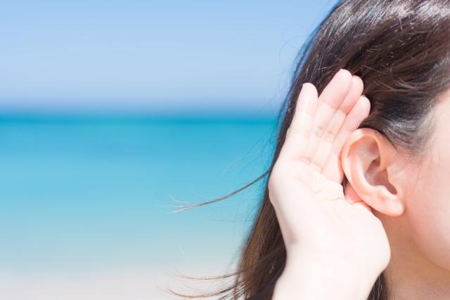 耳に手を当てて、よく聞こうとする人