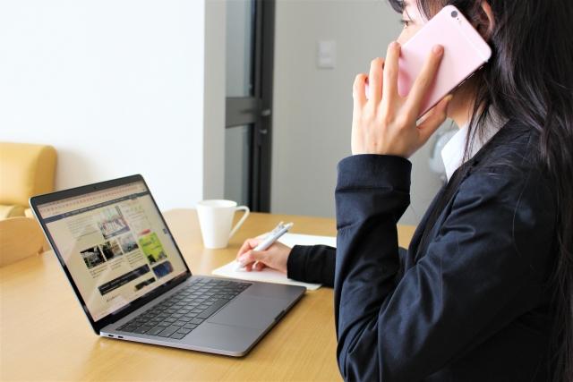 電話しながらパソコンを見ている女性