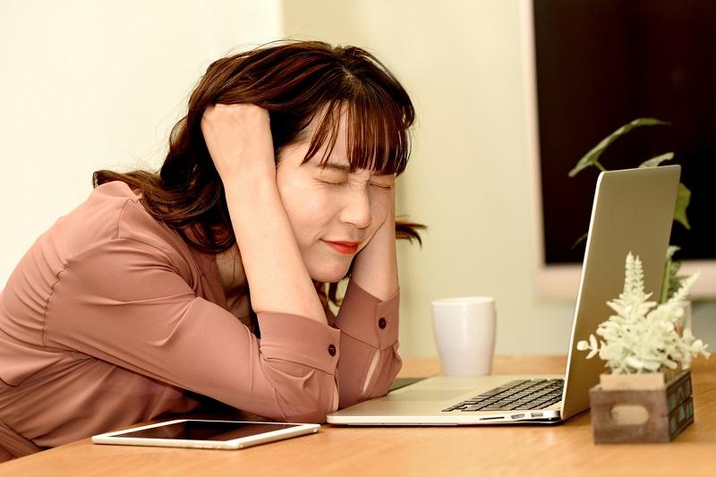 パソコンの前で困っている女性