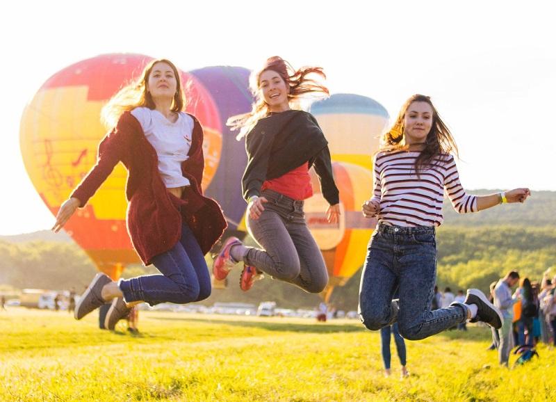 女性3人が気球の前でジャンプしている