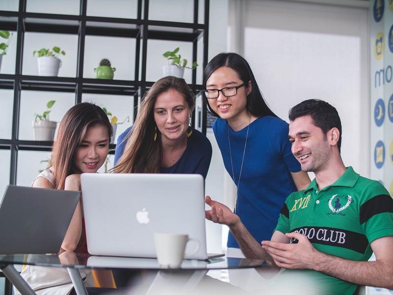 4人の男女が1つのパソコンを見ている