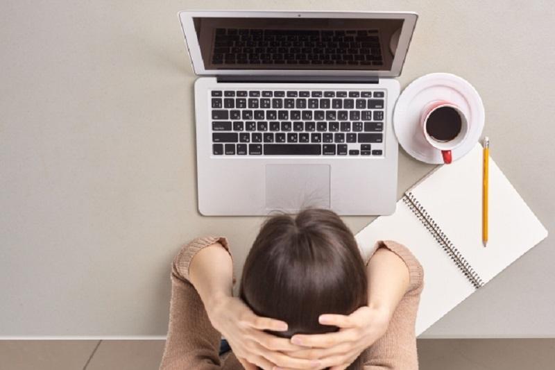 パソコンの前で頭を抱えている女性